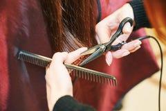 专业美发师的手有剪刀和梳子的 免版税图库摄影