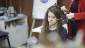 专业美发师,做相当青少年的女孩的美发师卷毛白色的腾出空位 股票录像