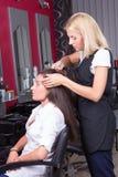 专业美发师画象在美容院的工作 免版税库存图片