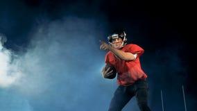 专业美国橄榄球运动员拿到一个球,当站立在领域时 股票录像