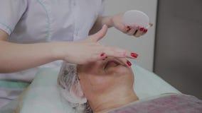 专业美容师应用防护奶油于年长妇女在美容院里 影视素材