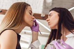 专业美容师画象做永久眼眉的紫色手套的 免版税库存图片