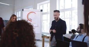专业老练的中部年迈的CEO商人讲话在不同种族的队的现代时髦办公室研讨会 股票视频
