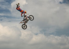 专业自由式摩托车越野赛车手执行与摩托车的一个把戏在蓝色云彩天空的背景 德语Stuntda 库存图片