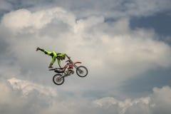 专业自由式摩托车越野赛车手执行在一个跃迁的一个把戏与在蓝色云彩天空的背景的摩托车 毒菌 免版税库存照片
