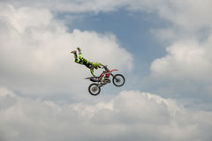 专业自由式车手执行与摩托车的一个把戏在蓝色云彩天空的背景 极其体育运动 德国St 免版税库存照片