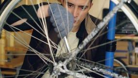 专业自行车安装工是转动它和调整与板钳的自行车车轮繁忙的定象机制 金属轮子 影视素材
