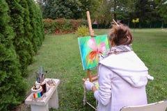 专业艺术家妇女写坐在有b的画架的图片 库存图片