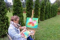 专业艺术家妇女写坐在有b的画架的图片 库存照片