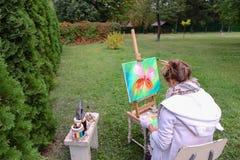 专业艺术家妇女写坐在有b的画架的图片 免版税库存照片