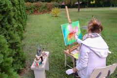 专业艺术家妇女写坐在有b的画架的图片 图库摄影