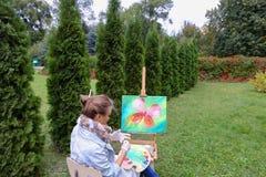 专业艺术家妇女写坐在有b的画架的图片 免版税图库摄影