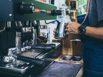 专业蒸与不锈钢杯子的barista佩带的牛仔裤围裙牛奶在咖啡机咖啡馆 库存图片