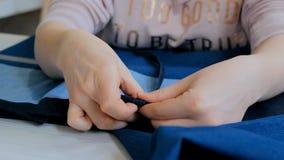 专业裁缝,缝合的设计师测量的衣服夹克在工作室 免版税库存照片
