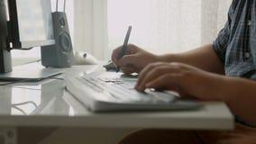 年轻专业设计师特写镜头与数字式图画片剂和键盘一起使用在办公室 股票视频