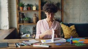 专业设计师通过有然后采取飞溅纸和选择颜色的设计样品的笔记本看为 影视素材