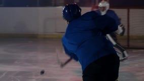 专业运动员男性曲棍球运动员在照相机前面转动与顽童并且触击对手的目标和 股票录像