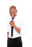 专业非洲人用在他的领带的手 库存照片