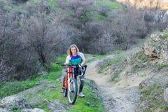 专业骑自行车者在山的上面,竞争的起点上升 库存图片