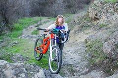 专业骑自行车者在山的上面,竞争的起点上升 免版税库存照片