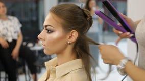 专业头发梳妆台使用的头发平直的铁直挺器头发 股票视频