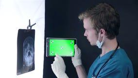 专业医生与X-射线扫描和片剂一起使用有绿色屏幕的 影视素材
