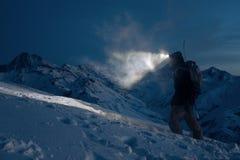 专业expeditor做在多雪的山的攀登在夜和光里与前灯的方式 佩带的滑雪穿戴,背包和 库存图片