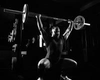 专业powerlifter举在他的头上的酒吧在蹲坐 免版税库存图片