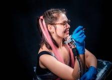 专业tattooer为照相机摆在纹身花刺演播室 库存图片