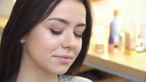 专家在逗人喜爱的青少年的女孩的面孔组成应用化妆用品的艺术家护肤和健康脸色的 影视素材