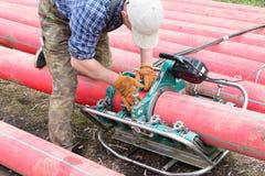 专家安装塑料管子对接焊的一个焊接器  电缆的聚乙烯管子 库存照片