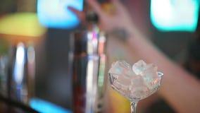 专家的男服务员做鸡尾酒在夜总会 专业侍酒者在倾吐甜饮料的酒吧的工作入玻璃  股票录像