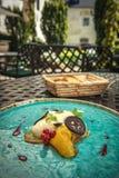 专属乳酪奶油甜点用用卤汁泡的核桃和金黄甜菜根在绿松石板材,顶面美食术服务 免版税图库摄影