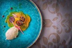 专属乳酪奶油甜点用用卤汁泡的核桃和金黄甜菜根在绿松石板材,顶面美食术服务 库存照片