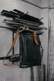 专属黑皮革背包 在墙壁附近的背包 在车库的工具 在墙壁附近的金属管子 图库摄影