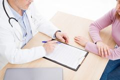 专心地听一位男性医生的患者解释耐心症状或问问题,他们一起谈论文书工作 免版税库存图片