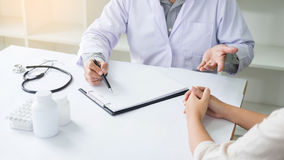 专心地听一名男性医生解释的患者s的患者 免版税库存照片