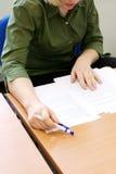 专心地读妇女的文件 免版税图库摄影