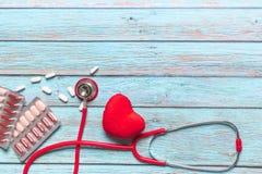 世界卫生日医疗保健和医疗概念红色听诊器和医学在蓝色木背景 库存图片