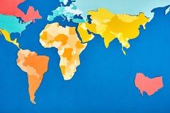 世界地图删去了颜色纸带盘座在蓝色 库存照片