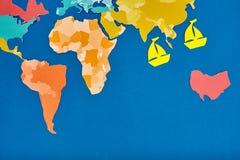 世界地图和两艘船删去了颜色纸带盘座在蓝色 免版税库存图片