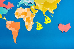 世界地图被删去色纸和两根据蓝色的删去了黄色纸船 免版税库存图片