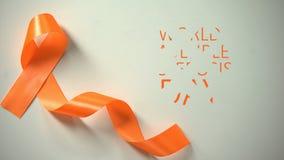 世界多发性硬化症天题字,在桌上的女性安置的橙色丝带 股票录像