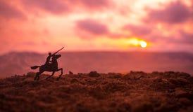 世界大战在马的官员(或战士)车手与准备好黑暗的有雾的被定调子的背景的剑战斗和战士 争斗sc 库存照片