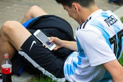 世界杯2018年 莫斯科国际足球联合会2018年 足球迷的情感在莫斯科街道上的 Messi一件年轻人佩带的制服与电话的 免版税库存照片