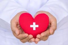 世界献血者天, 6月14日 拿着红色心脏的医生手 免版税库存照片