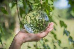 世界环境概念 水晶地球在美好的绿色和蓝色bokeh的人的手上 免版税库存图片