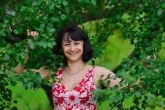 世界的最愉快的妇女与站立在绿色树的惊人的美好的白色微笑夏令时 美丽有吸引力前 库存图片