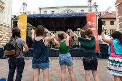 世界青年日的香客在圣玛丽亚马格达莱纳广场唱歌并且跳舞在克拉科夫 库存照片