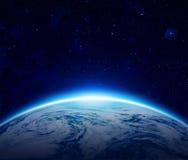 世界,在多云海洋的蓝色行星地球日出 免版税库存照片
